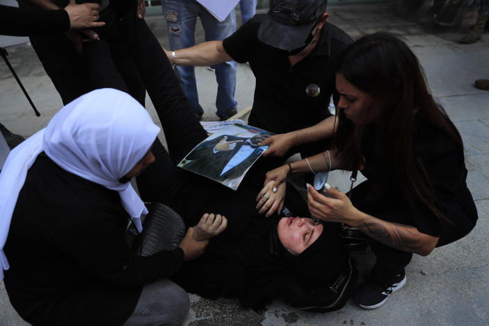 Families of the victims of last year's massive blast at Beirut's seaport, treat a woman who fell down while she was trying with others to reach the tightly-secured residents of parliament speaker Nabih Berri and was pushed back by Lebanese army soldiers, in Beirut, Lebanon, Friday, July 9, 2021. The protest came after last week's decision by the judge to pursue senior politicians and former and current security chiefs in the case, and requested permission for their prosecution. (AP Photo/Hussein Malla)