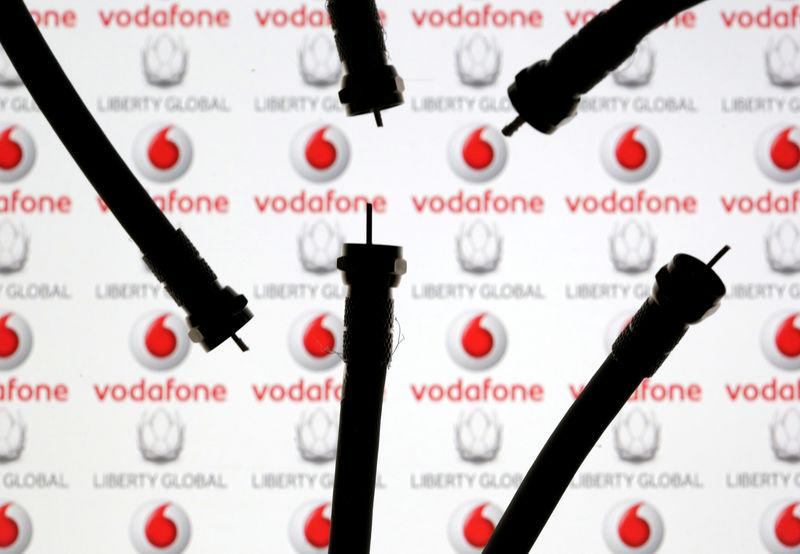FILE PHOTO: Coaxial TV Cables are seen in front of Vodafone and Liberty Global logos in this illustration