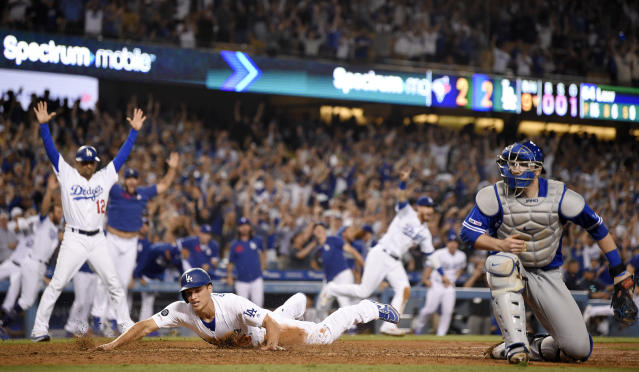 Los Angeles Dodgers' Corey Seager, center, scores the winning run on a single by Enrique Hernandez, as Toronto Blue Jays catcher Danny Jansen, right, misses the throw during the ninth inning of a baseball game Thursday, Aug. 22, 2019, in Los Angeles. The Dodgers won 3-2. (AP Photo/Mark J. Terrill)
