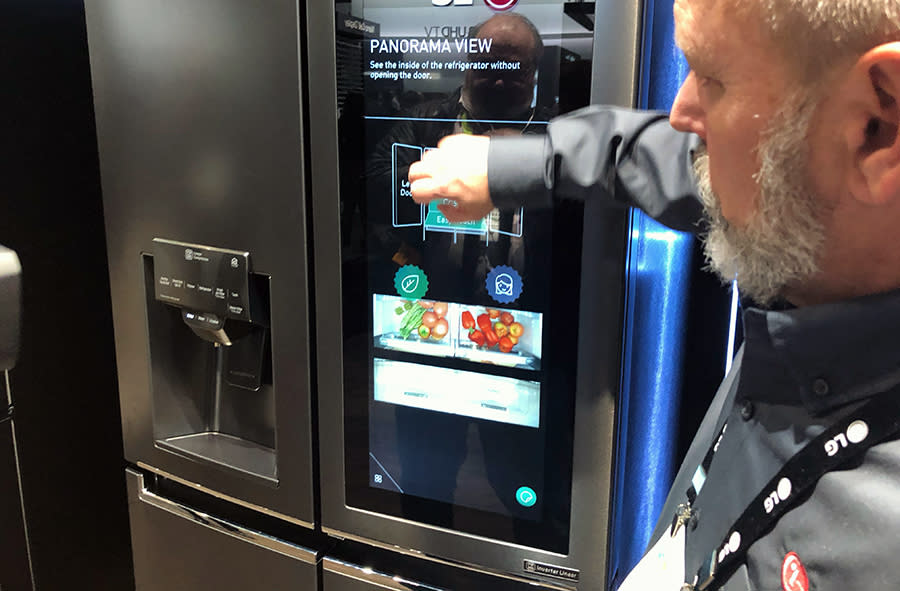 An LG employee shows how its new fridge has six cameras inside that let you see its contents.