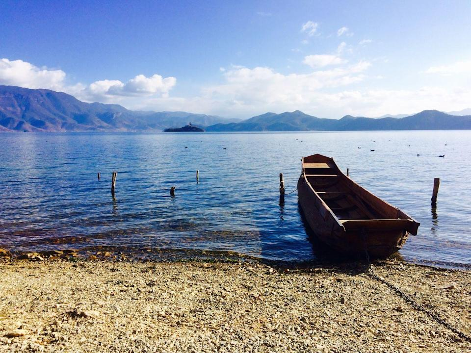 <p>A wooden boat rests on the shore of Lugu Lake in Yunnan, China.</p>