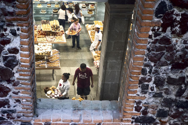 <p>People fill trays of pastries at a sweets shop. Mexico has a very high level of child obesity cases, and an increasing rate of type 2 diabetes among children. (Photograph by Silvia Landi) </p>