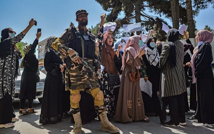 A Taliban fighter stands guard as Afghan women shout slogans during an anti-Pakistan protest rally, near the Pakistan embassy in Kabul - AFP