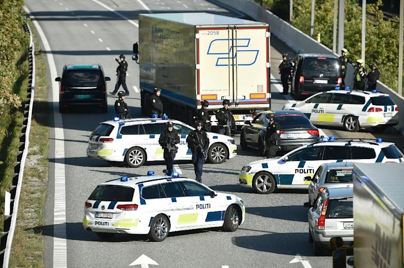 Police block a road to the Oresund Bridge which connects Denmark and Sweden on Friday as part of a massive manhunt