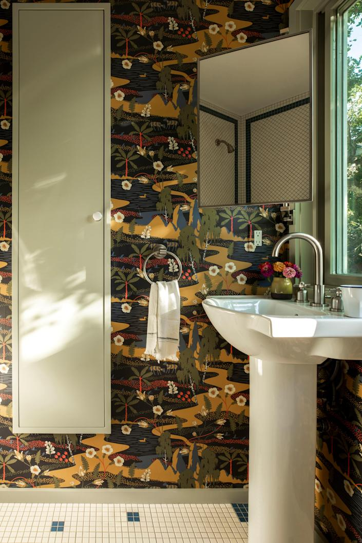 """""""This intricate wallpaper has a storybook quality to it,"""" says Carter of the Boråstapeter paper she used in the kids bathroom. """"There are so many little moments for a child to get lost in."""" The sink and fittings are by Kohler."""