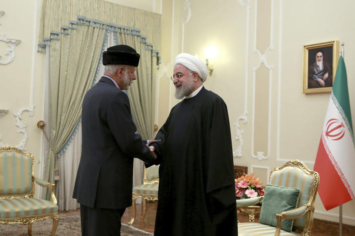 In this photo released by the official website of the office of the Iranian Presidency, President Hassan Rouhani, right, shakes hands with Omani Minister of State for Foreign Affairs Yusuf bin Alawi at the start of their meeting, in Tehran, Iran, Tuesday, Dec. 3, 2019 (Office of the Iranian Presidency via AP)