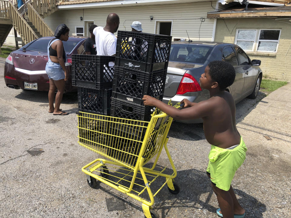 Christopher Williams, 5, pushes a shopping cart outside his family's destroyed apartment in Luling, La., on Tuesday, Sept. 7, 2021. Williams, and his two brothers stack milk crates in a vacant parking lot to pass time because their toys were swept away by Hurricane Ida. They are among an estimated 250,000 children across Louisiana with no school to go to after the storm left them shuttered. (AP Photo/Matt Sedensky)