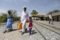 People cross a railway track at Vadnagar railway station in Gujarat March 26, 2014. REUTERS/Amit Dave