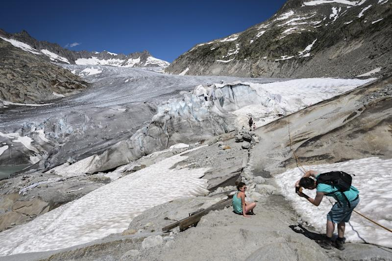 Tourists pose on the Rhone Glacier near Gletsch (AFP Photo/Fabrice Coffrini)