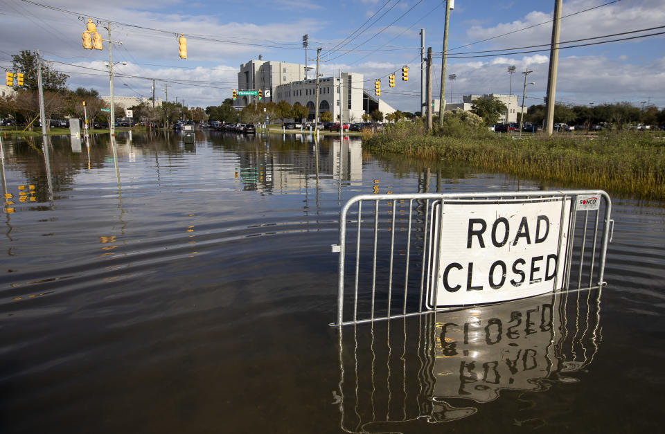 A road closed sign tells motorist to not pass through the flood waters at the intersection of Fishburne St. and Hagood Ave. as a king tide rolls into historic Charleston, S.C. Sunday, Nov. 15, 2020. Charleston has remained relatively unscathed this hurricane season. That means more time to mull a $1.75 billion proposal by the Army Corps of Engineers that features a sea wall along the city's peninsula to protect it from deadly storm surge during hurricanes. (AP Photo/Mic Smith)