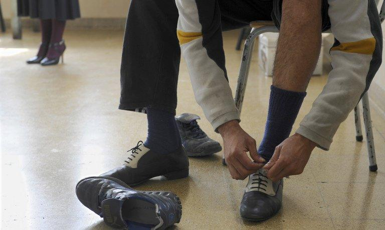 A man replaces his running shoes for tango shoes at a tango-therapy session at Borda hospital in Buenos Aires on September 23, 2009. Some health centers in Buenos Aires have found that the complex 2/4 beat can help soothe patients, including those suffering from mental ailments, forcing them to focus their minds on an activity that requires, well, two to tango