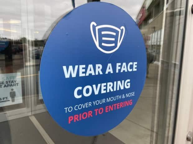 A sign instructs people to wear a face covering before entering a building.  (CBC - image credit)