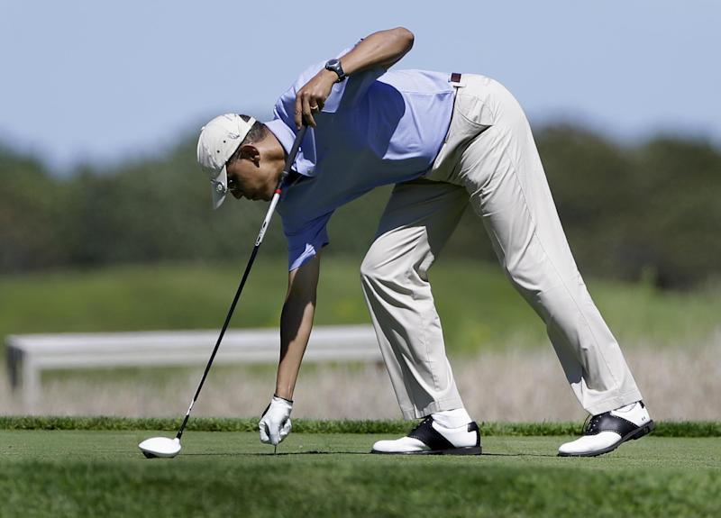 President Barack Obama prepares to tee off while golfing at Vineyard Golf Club in Edgartown, Mass., on the island of Martha's Vineyard Wednesday, Aug. 14, 2013. President Obama and his wife Michelle are vacationing on the island. (AP Photo/Steven Senne)