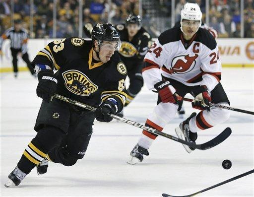 Boston Bruins left wing Brad Marchand (63) controls the puck against New Jersey Devils defenseman Bryce Salvador (24) during the second period of an NHL hockey game in Boston, Tuesday, Jan. 29, 2013. (AP Photo/Charles Krupa)