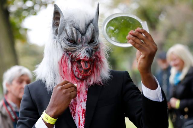 <p>A participant checks their costume before taking part in a in a zombie walk on World Zombie Day in London on Oct. 7, 2017. (Photo: Tolga Akmen/AFP/Getty Images) </p>