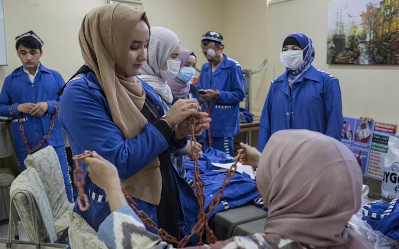 Uighur activists try on plastic chains and imitation prison uniforms ahead of a demonstration outside the Chinese embassy in Istanbul, Turkey - Sam Tarling for The Telegraph