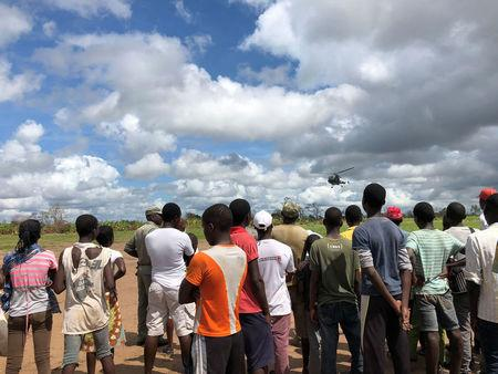 Locals watch as a helicopter lands in Guara Guara after Cyclone Idai outside Beira
