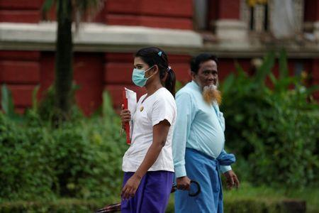 A woman wears a mask on his face to protect herself from H1N1 in Yangon, MyanmarJuly 24, 2017. REUTERS/Soe Zeya Tun