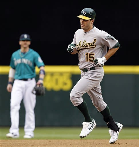 Oakland Athletics' Seth Smith (15) rounds the bases past Seattle Mariners shortstop Brendan Ryan on a second-inning home run in a baseball game, Monday, June 25, 2012, in Seattle. (AP Photo/Elaine Thompson)