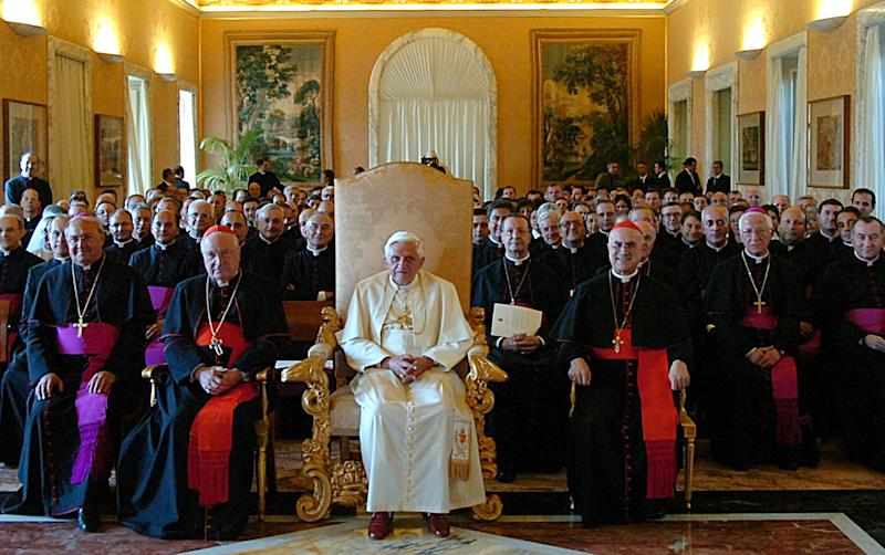 """FILE - This Sept. 15, 2006 file photo released by the Vatican's newspaper L'Osservatore Romano shows Pope Benedict XVI, at center, presiding a meeting with outgoing Vatican Secretary of State Cardinal Angelo Sodano, left foreground in red, and the new Vatican's No. 2 official Cardinal Tarcisio Bertone, right foreground in red, during a meeting at the Vatican. After 35 years under two """"scholar'' popes who paid scant attention to the internal governance of the Catholic Church, a chorus is growing that the next pontiff must have a solid track record managing a complicated bureaucracy.  Benedict was well aware of the problems, having spent nearly a quarter-century in the Vatican's Congregation for the Doctrine of the Faith. But he never entered into the Vatican's political fray as a cardinal _ and as pope left it to his No. 2, Cardinal Tarcisio Bertone, to do the job. (AP Photo/L'Osservatore Romano, ho, files)"""