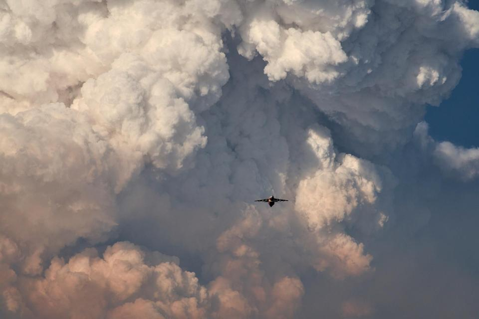 A firefighting aircraft returns to base amid massive plumes of smoke after dropping flame-retarding chemicals on the Bootleg Fire in Bly, Oregon, on July 15.