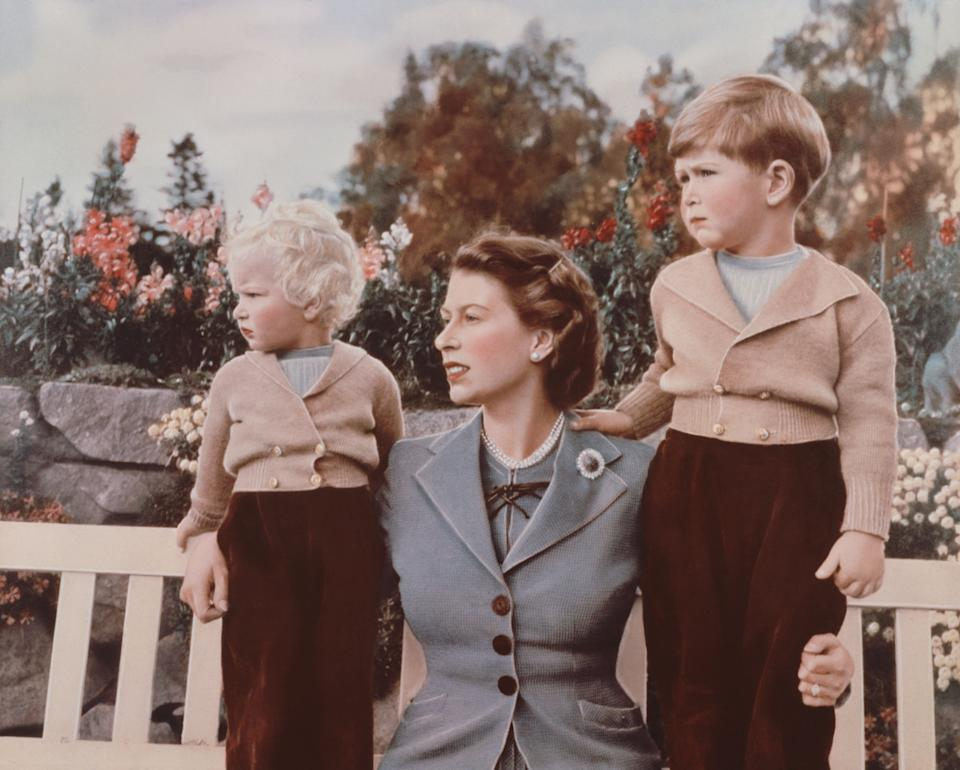 Elizabeth with Prince Charles and Princess Anne on the grounds of Balmoral Castle, Scotland. Charles was celebrating his 4th birthday.