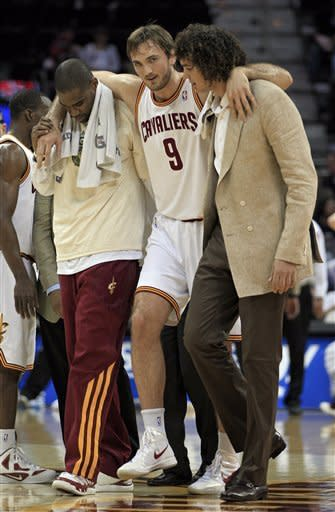 Cleveland Cavaliers' Semih Erden, from Turkey, is helped off the floor by Antawn Jamison, left, and Anderson Varejao after injuring his ankle in the second quarter of an NBA basketball game against the Indiana Pacers on Wednesday, April 11, 2012, in Cleveland. (AP Photo/Mark Duncan)