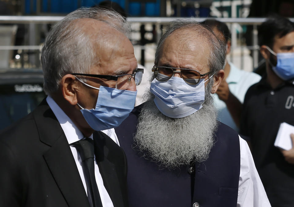 Ahmed Saeed Sheikh, right, father of a British-born militant Ahmed Omar Saeed Sheikh, leaves the Supreme Court with his lawyer Mahmood Ahmed Sheikh, left, after an appeal hearing in the Daniel Pearl case, in Islamabad, Pakistan, Wednesday, Oct. 7, 2020. Ahmed Omar Saeed Sheikh, who has been on death row over the 2002 killing of U.S. journalist Daniel Pearl, will remain in jail for another three months under a government order, a prosecutor told the country's top court Wednesday as it took up appeals of Pearl's family and government against acquittal of all accused of murder charges by another court. (AP Photo/Anjum Naveed)