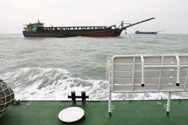 Sand-dredging ships with Chinese flags are seen from a Taiwanese coast guard ship patrolling in the waters off the Taiwan-controlled Matsu islands