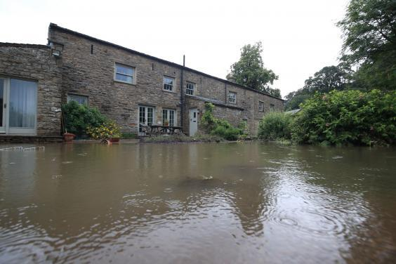 A flooded house in North Yorkshire, where more than 100 homes have been swamped (PA)