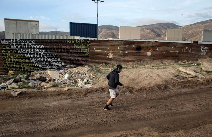 A man jogs on the Mexican side of the Mexico-US border in Tijuana, from where prototypes of the wall that US President Donald Trump wants to build are visible (AFP Photo/GUILLERMO ARIAS)