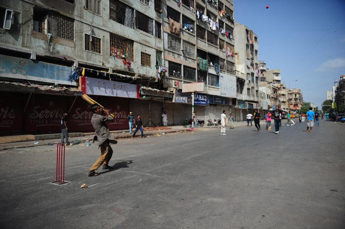 Pakistani youth play cricket on a street during a strike in Karachi on June 22, 2013, to protest the killing of lawmaker Sajid Qureshi. Gunmen on June 21, shot dead a Pakistani lawmaker, his son and a passer-by outside a mosque in the country's business capital of Karachi, officials said. AFP PHOTO/ Asif HASSAN
