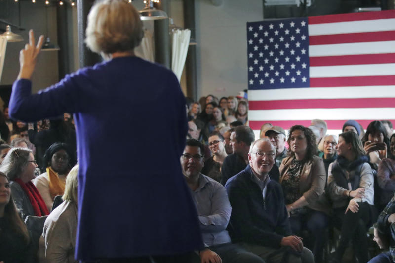 FILE - In this Jan. 10, 2020, file photo, Bruce Mann, husband of Democratic presidential candidate Sen. Elizabeth Warren, D-Mass., right, smiles as he listens to his wife during a campaign stop in Dover, N.H. (AP Photo/Charles Krupa, File)
