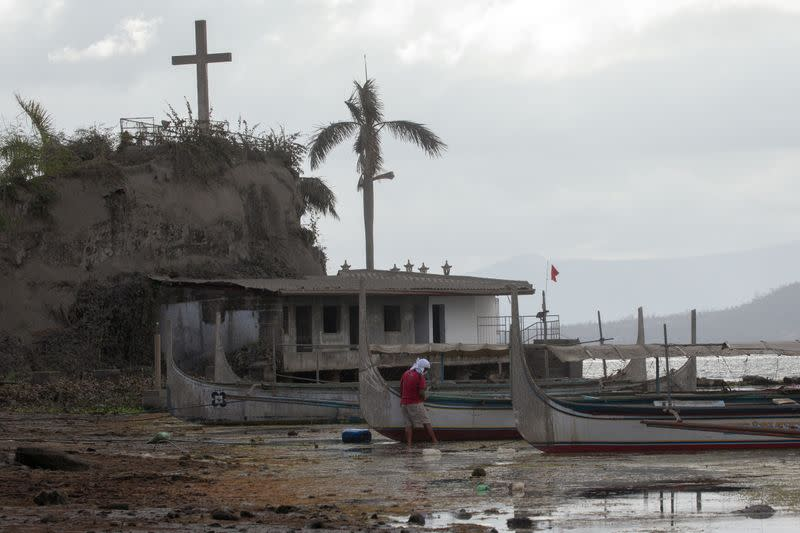 A man cleans his boat in an ash-covered fishing port in Talisay