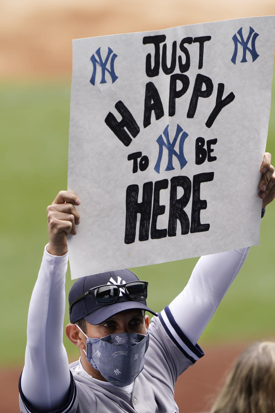 A fan holds a sign expressing his joy at being able to attend a major league baseball game between the New York Yankees and the Toronto Blue Jays on opening day at Yankee Stadium, Thursday, April 1, 2021, in New York. (AP Photo/Kathy Willens)