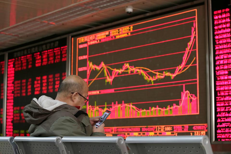 An investor looks at his mobile phone in front of a board showing stock information at a brokerage office in Beijing, China January 2, 2020. REUTERS/Jason Lee