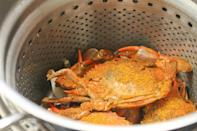 <p>After making sure the crabs are still alive, set up a double-boiler or steamer. Boil a little bit of water, add your crabs and double-check that the crabs are only exposed to steam, not water so as not to make the meat soggy. Once the crabs are in, apply a very liberal amount of Old Bay, cover and cook for about 12 to 15 minutes, depending on the crabs' size. When they're bright red, they're done. </p>
