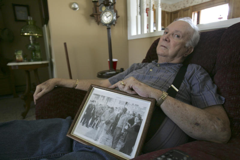 """FILE - In this Wednesday, March 4, 2009, file photo, Elwin Hope Wilson holds a framed photo he kept showing a mob he participated in during one of local civil rights """"sit-ins"""" that took place in the early 1960s, in Rock Hill, S.C.  The South Carolina man who publicly apologized for years of violent racism, including the beating of a black Freedom Rider who went on to become a Georgia congressman, died Sunday, March 31, 2013. He was 76. (AP Photo/Mary Ann Chastain)"""