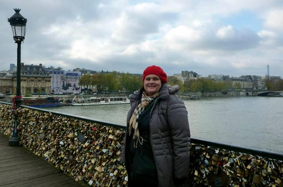 A photo of Sydney woman Maria wearing a grey coat and red beanie on a bridge covered in locks