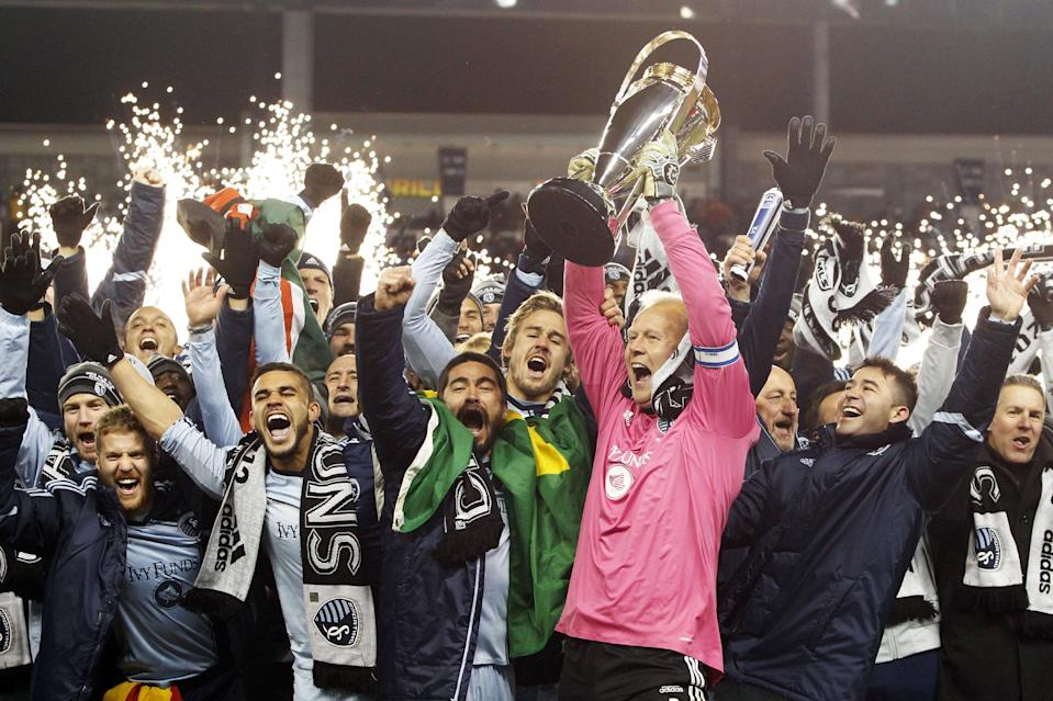 Sporting Kansas City goalkeeper Jimmy Nielsen, center, holds the MLS Cup as he and his teammates celebrate their 2-1 win over Real Salt Lake in the MLS Cup soccer championship in Kansas City, Kan., Saturday, Dec. 7, 2013. Kansas City won after a 7-6 penalty kick shootout. (AP Photo/Colin E. Braley)