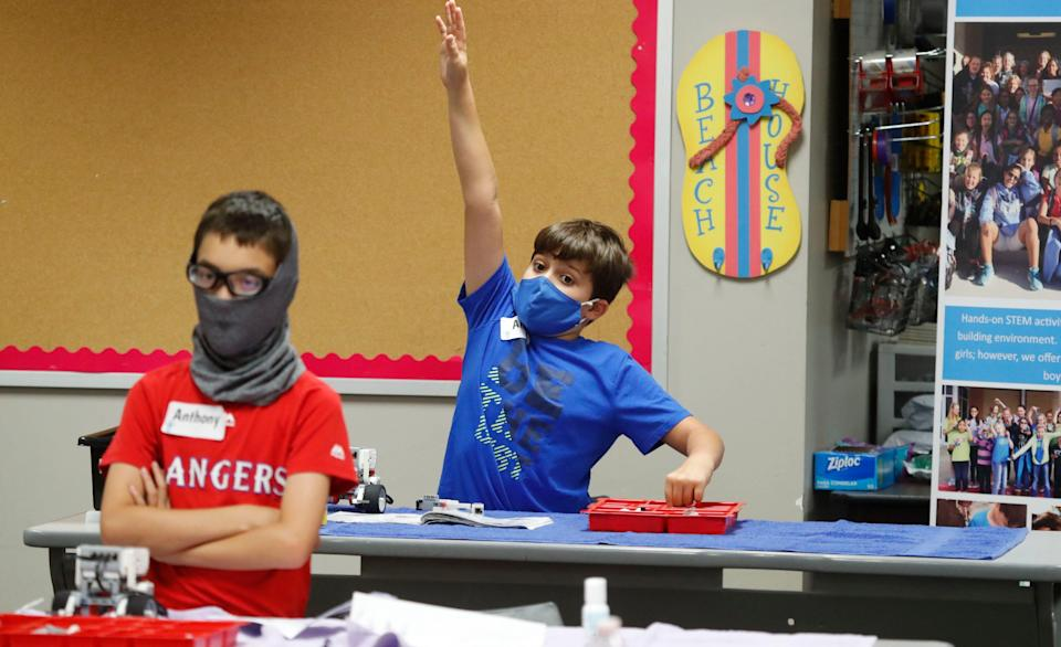 Amid concerns about the spread of COVID-19, Aiden Trabucco, right, and Anthony Gonzales wear face coverings during a summer STEM camp at Wylie High School on July 14 in Wylie, Texas.