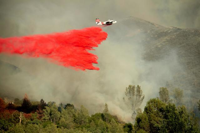 <p>An air tanker drops retardant on a wildfire burning above the Spring Lakes community on Sunday, June 24, 2018, near Clearlake Oaks, Calif. Wind-driven wildfires destroyed buildings and threatened hundreds of others Sunday as they raced across dry brush in rural Northern California. (Photo: Noah Berger/AP) </p>