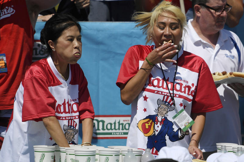 Juliet Lee, left, and Miki Sudo, right, compete in the women's competition of Nathan's Famous July Fourth hot dog eating contest, Thursday, July 4, 2019, in New York's Coney Island. (AP Photo/Sarah Stier)