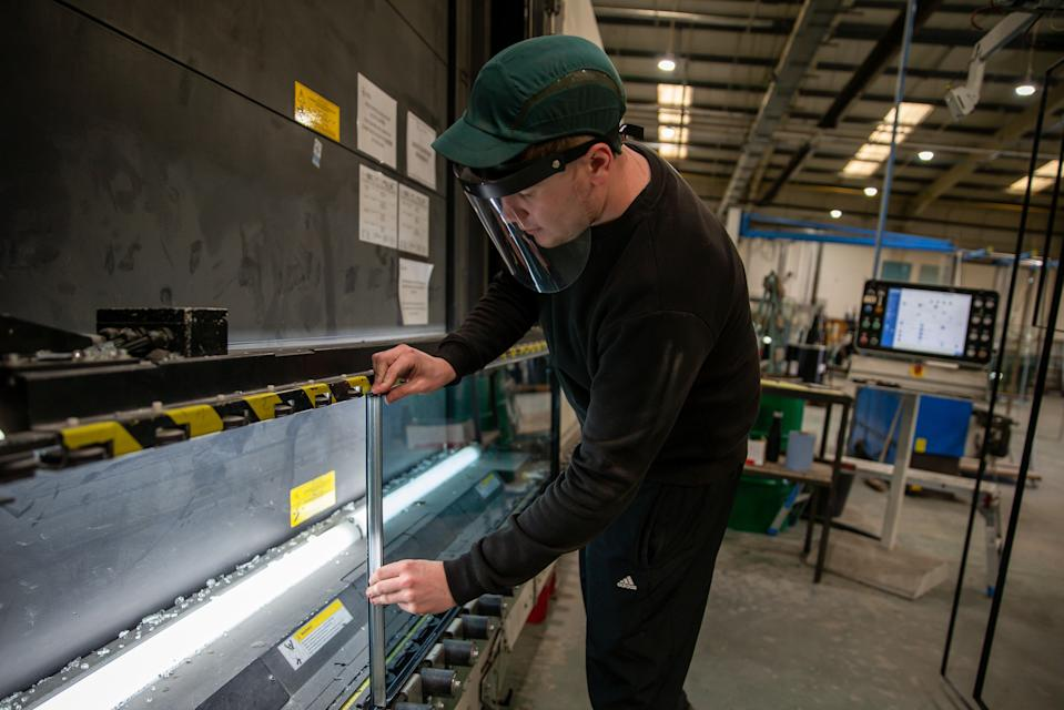 EBBW VALE, WALES, - SEPTEMBER 25:  A general view of a member of staff at Cwmtillery Glass factory placing a spacer on the units before being filled with argon gas and sealed as a unit on September 25, 2020 in Ebbw Vale, Wales United Kingdom. (Photo by Huw Fairclough/Getty Images)