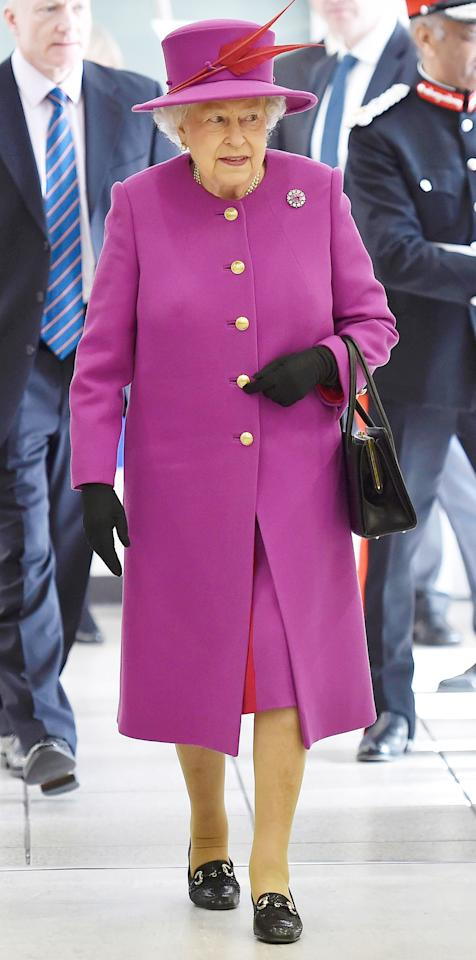 <p>The monarch dazzled in a magenta coat and top hat adorned with two red feathers on a visit to the Lister Community School.</p>