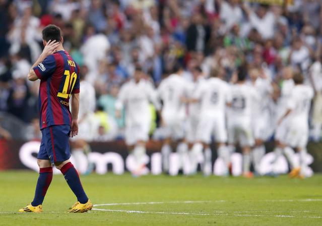 "Barcelona's Lionel Messi (L) looks on as Real Madrid's players celebrate their second goal during their Spanish first division ""Clasico"" soccer match at the Santiago Bernabeu stadium in Madrid October 25, 2014. REUTERS/Juan Medina (SPAIN - Tags: SOCCER SPORT)"