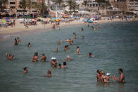 Bathers enjoy the beach in Palma de Mallorca, Spain, Sunday, July 26, 2020. Britain has put Spain back on its unsafe list and announced Saturday that travelers arriving in the U.K. from Spain must now quarantine for 14 days. The move by the UK taken without forewarning has caught travelers off guard. (AP Photo/Joan Mateu)
