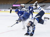Toronto Maple Leafs right wing Mitchell Marner (16) scores on an empty net and takes a hit from Winnipeg Jets defenseman Neal Pionk (4) during third-period NHL hockey game action in Toronto, Ontario, Monday, Jan. 18, 2021. (Nathan Denette/The Canadian Press via AP
