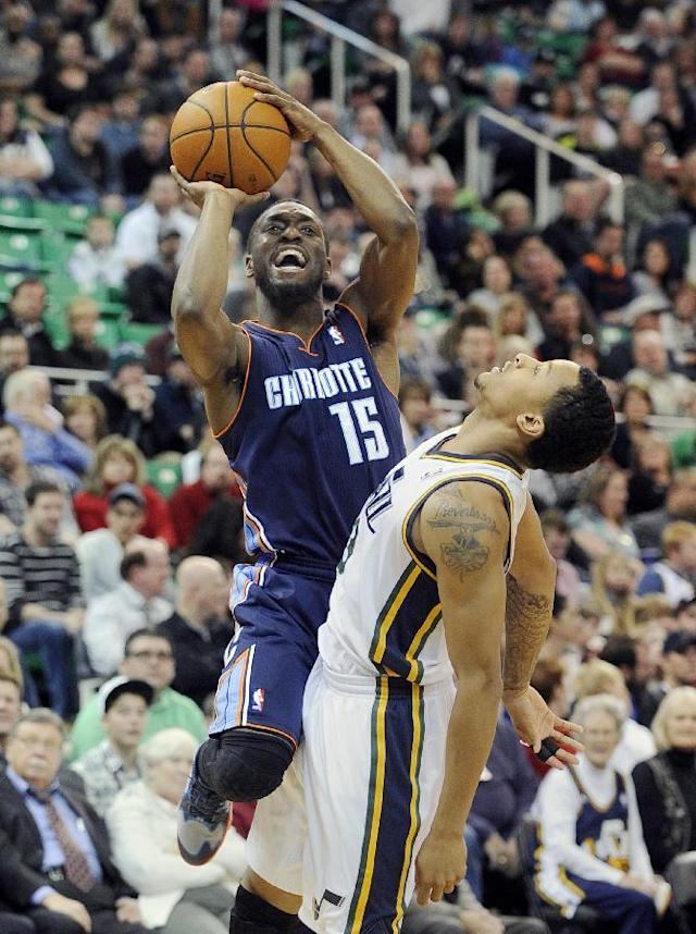 Charlotte Bobcats' Kemba Walker (15) shoots while colliding with Utah Jazz's Trey Burke, right, in the second quarter of an NBA basketball game Monday, Dec. 30, 2013, in Salt Lake City. (AP Photo/Gene Sweeney Jr.)
