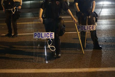 Police officers in riot gear stand in position as demonstrators protest the shooting death of Michael Brown, in Ferguson, Missouri